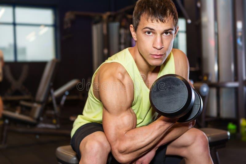 Ung man som övar med vikt i idrottshallen arkivbilder