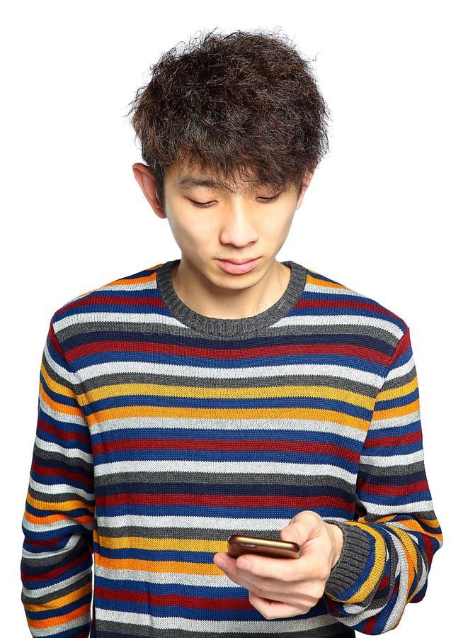 Ung man som använder att smsa för mobiltelefon arkivbilder