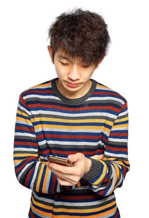 Ung man som använder att smsa för mobiltelefon royaltyfri foto