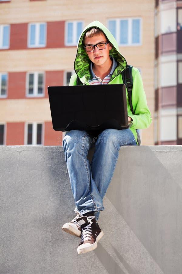 Ung man som använder bärbar dator arkivfoton