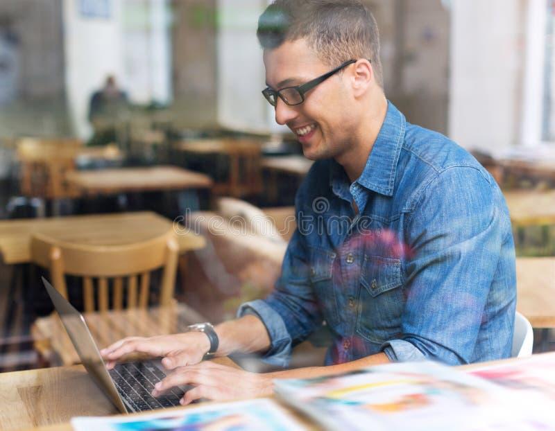 Ung man som använder bärbara datorn på kafét royaltyfri fotografi