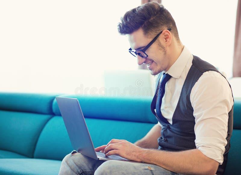 Ung man som använder bärbara datorn på soffan royaltyfri bild