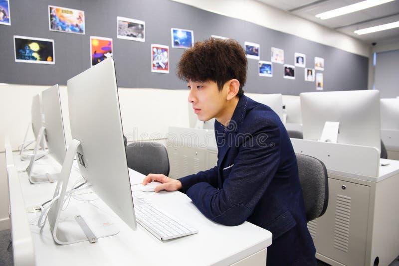 Ung man som använder datoren i klassrum royaltyfria bilder