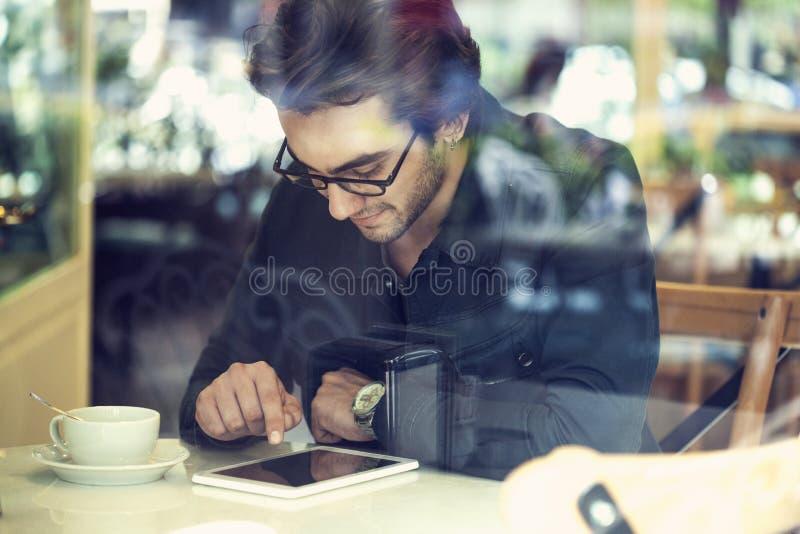 Ung man som använder den digitala minnestavlan i kafé royaltyfri bild