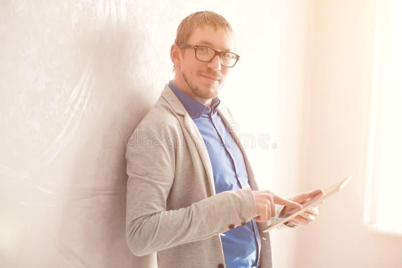 Ung man som använder den digitala minnestavlan mot väggen i solig dag royaltyfri fotografi