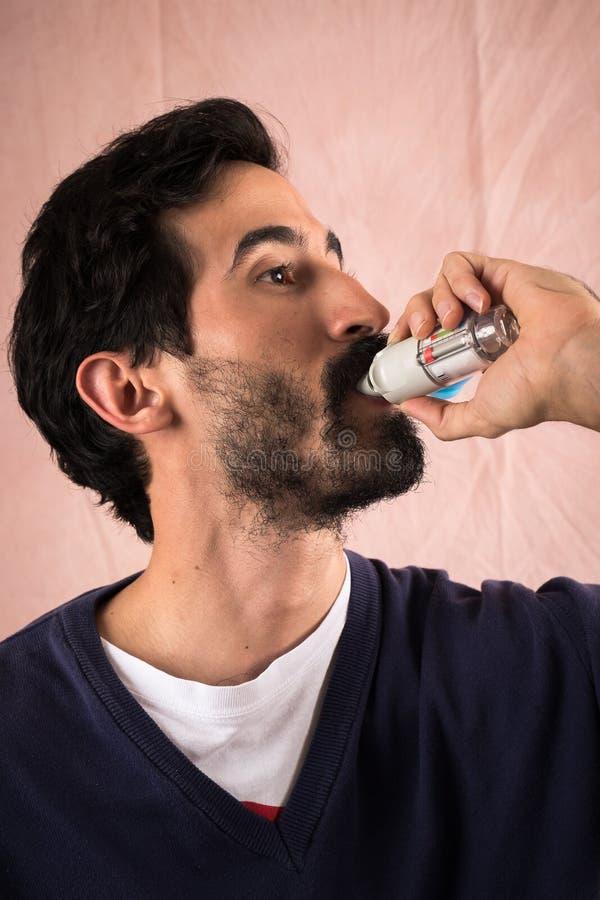 Ung man som använder en inhalator royaltyfria bilder
