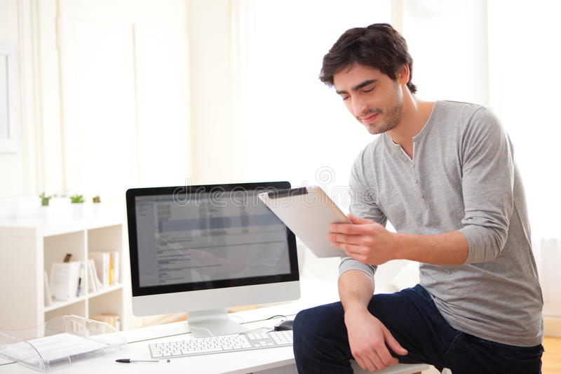 Ung man som använder en minnestavla på kontoret royaltyfria foton