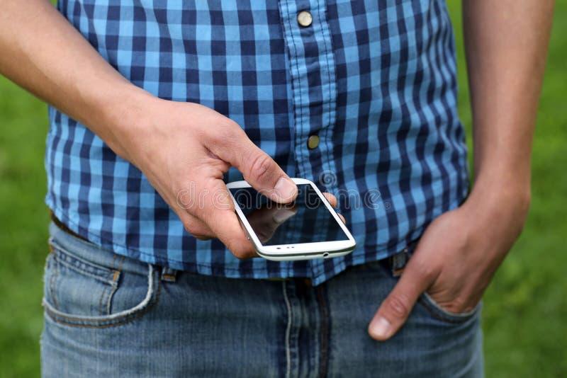 Ung man som använder en smartphone royaltyfria bilder