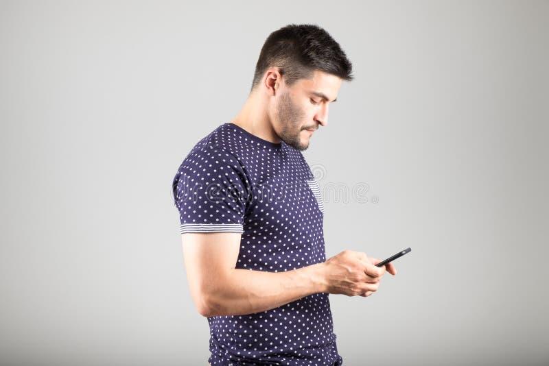 Ung man som använder hans smartphone arkivbilder