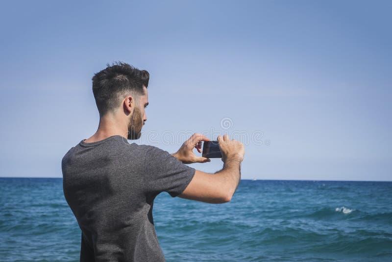 Ung man som använder mobiltelefonen för att ta fotoet på stranden royaltyfria bilder