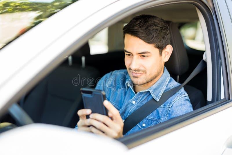 Ung man som använder mobiltelefonen i en bil royaltyfri bild