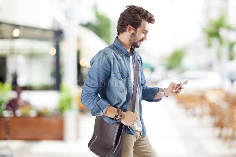 Ung man som använder mobiltelefonen i gata arkivfoto