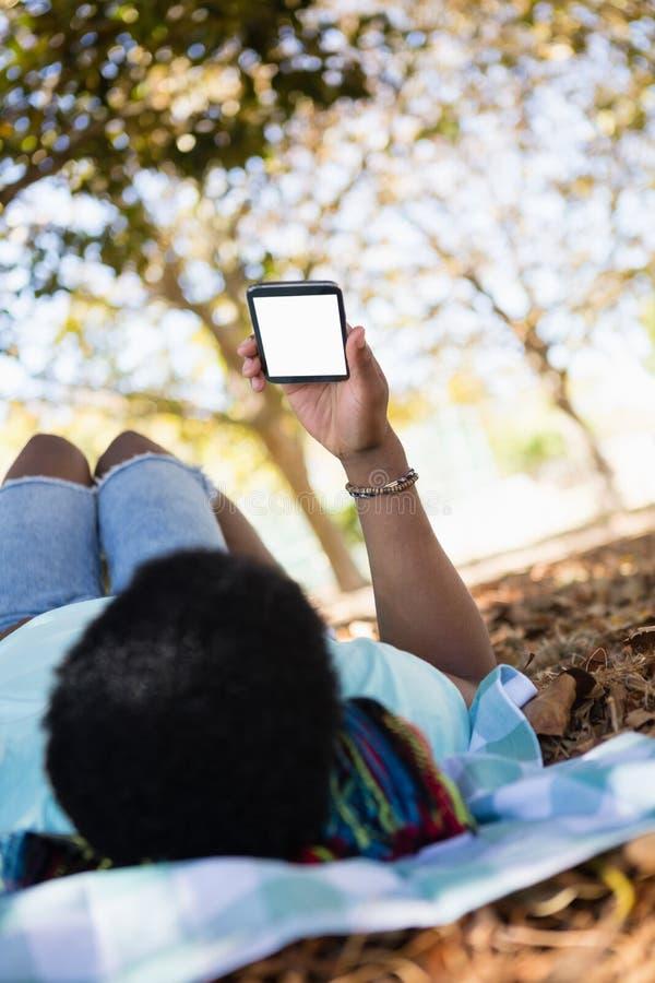 Ung man som använder mobiltelefonen, medan ligga på en picknickfilt arkivbilder