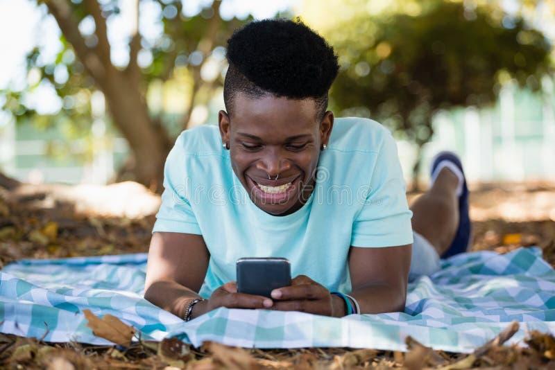Ung man som använder mobiltelefonen, medan ligga på en picknickfilt arkivfoto