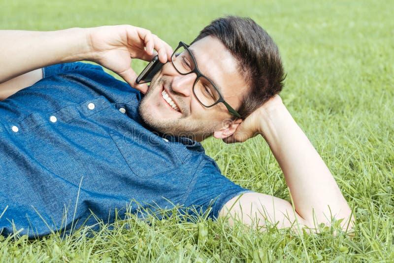 Ung man som använder mobiltelefonen, medan ligga på gräs royaltyfri bild