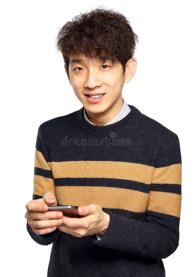 Ung man som använder mobiltelefonen på vit bakgrund royaltyfri foto