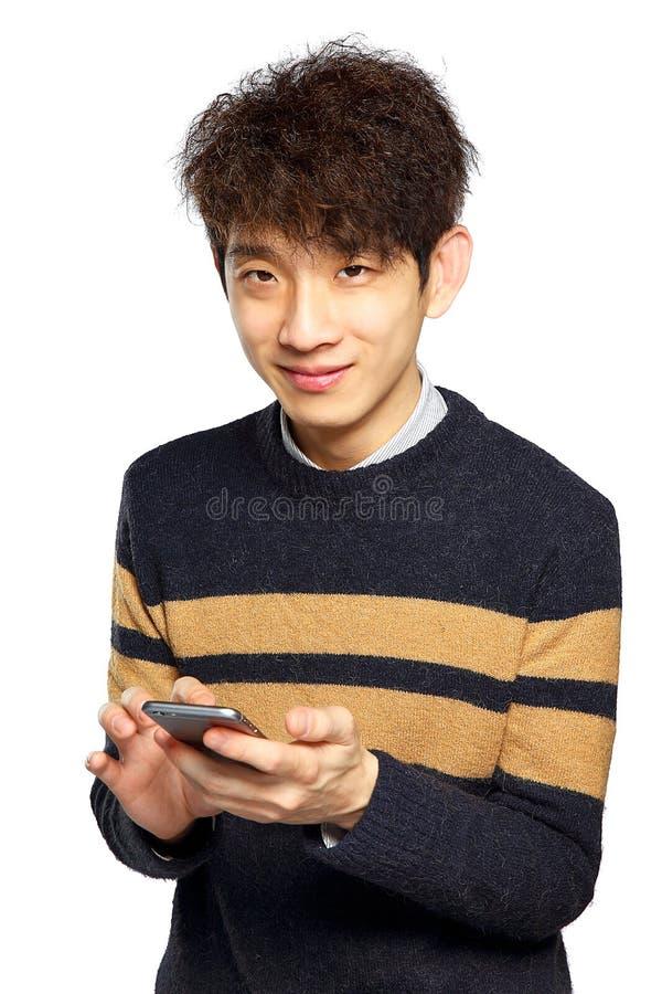 Ung man som använder mobiltelefonen på vit bakgrund arkivfoton