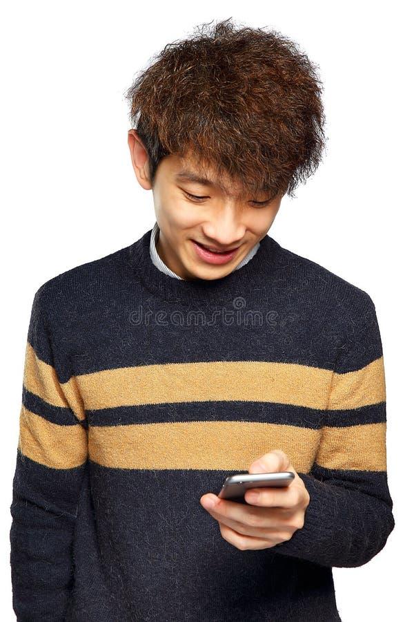 Ung man som använder mobiltelefonen på vit bakgrund arkivbild