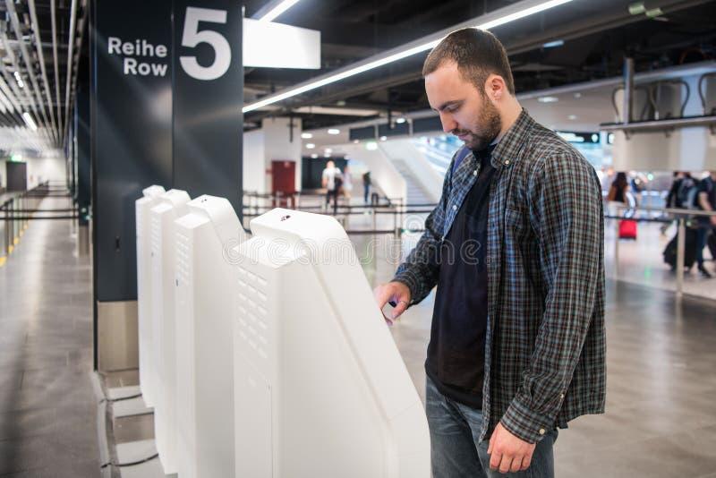 Ung man som använder själven - incheckningkiosk i flygplats arkivbilder