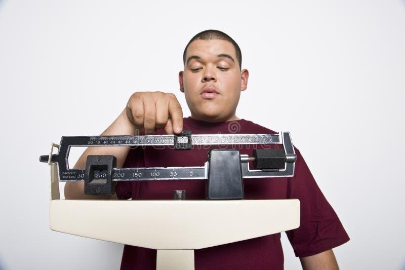 Ung man som använder viktvåg royaltyfri fotografi