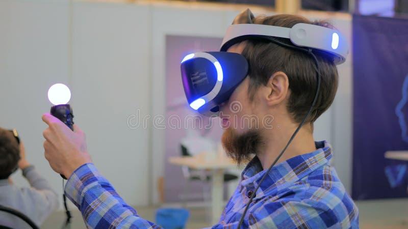 Ung man som använder virtuell verklighetexponeringsglas VR royaltyfria bilder