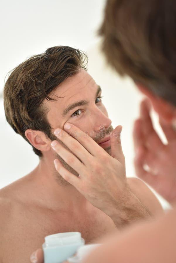 Ung man som applicerar ansiktsbehandlingkräm royaltyfri foto