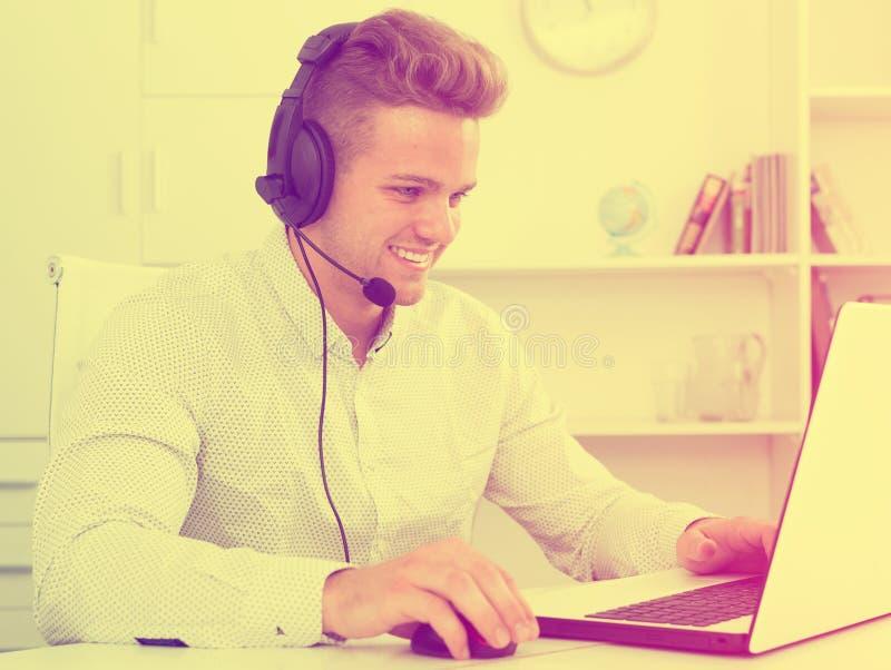 Ung man som arbetar i call center royaltyfri bild