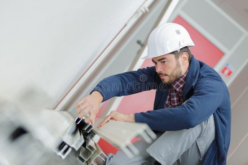 Ung man som arbetar med metallstänger i konstruktionsplats arkivfoto