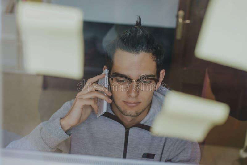 Ung man som arbetar och organiserar fotografering för bildbyråer
