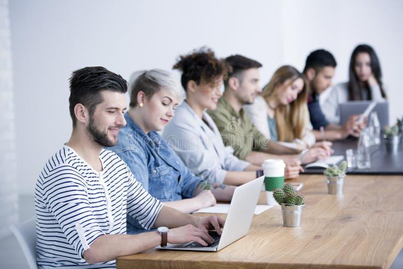 Ung man som arbetar på bärbara datorn royaltyfri foto