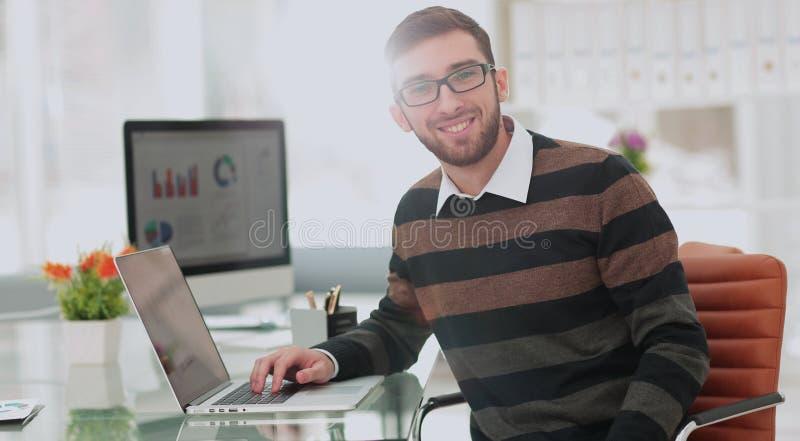 Ung man som arbetar på bärbara datorn modernt kontor Affärsprojekt royaltyfria foton