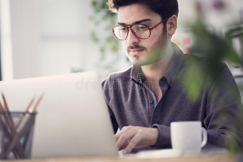 Ung man som arbetar på datoren arkivbilder