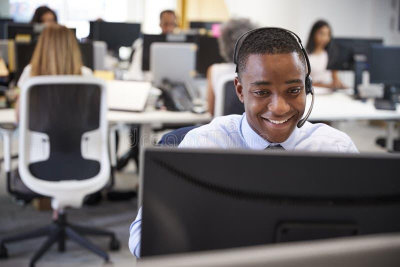 Ung man som arbetar på datoren med hörlurar med mikrofon i upptaget kontor arkivfoto