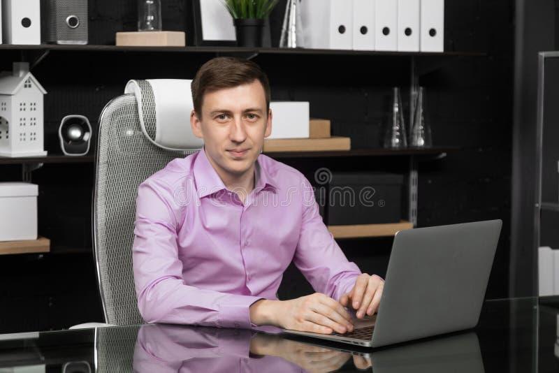 Ung man som arbetar på en bärbar dator i kontoret royaltyfria bilder