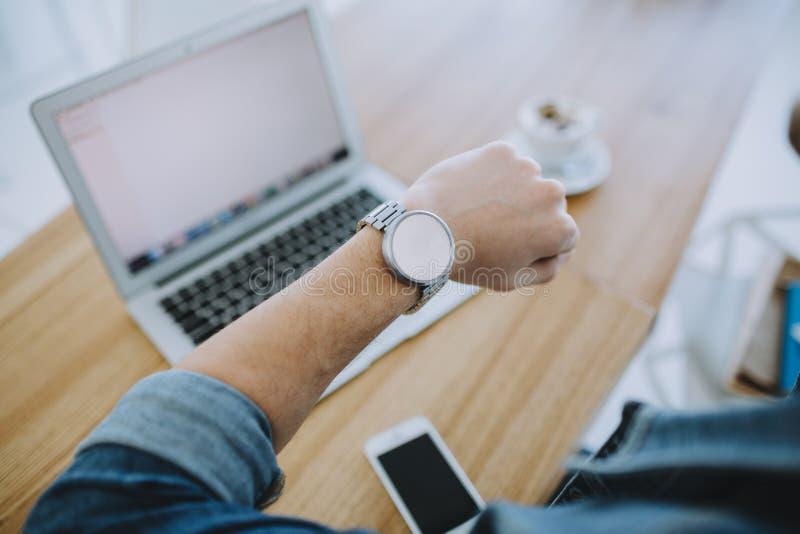 Ung man som arbetar på en macbook eller en bärbar dator i kafé royaltyfria bilder