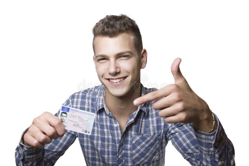 Ung man som av visar hans körkort royaltyfria foton