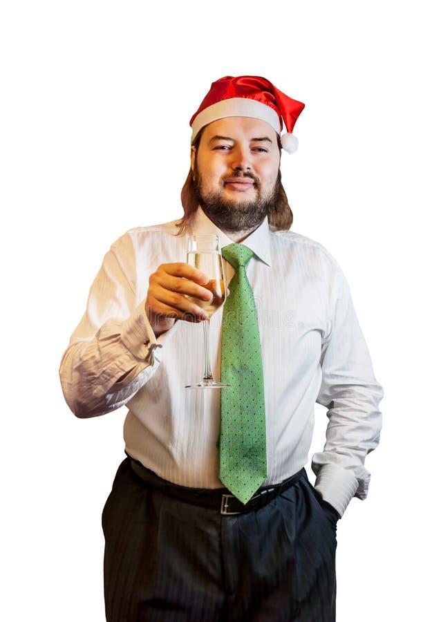 Ung man som bär en julhatt med isolerat exponeringsglas av champagne royaltyfri foto