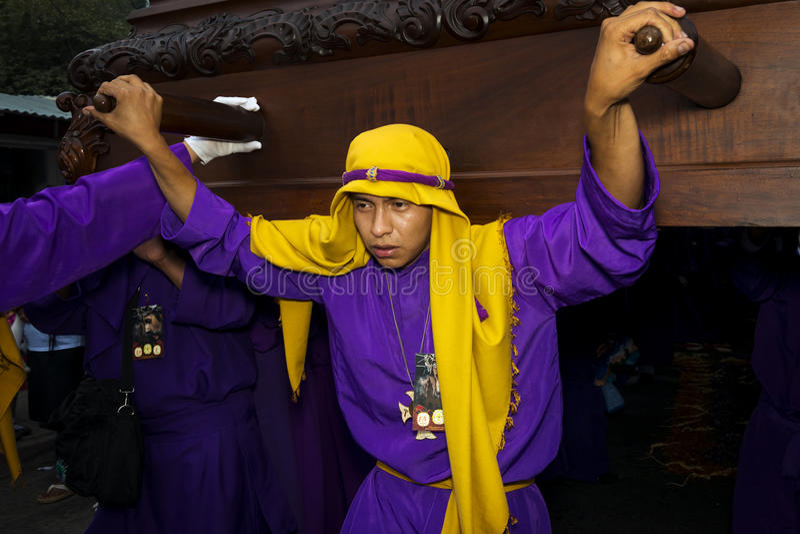 Ung man som bär en lila- och gulingämbetsdräkt som bär en flöteanda under påskberömmarna, i den heliga veckan, i Antigua, royaltyfri bild