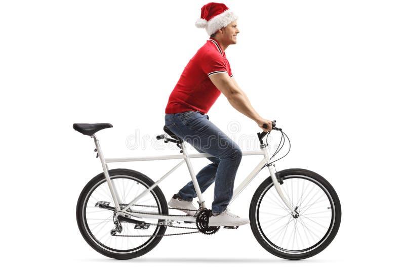 Ung man som bär en Santa Claus hatt och rider en tandem cykel royaltyfri bild