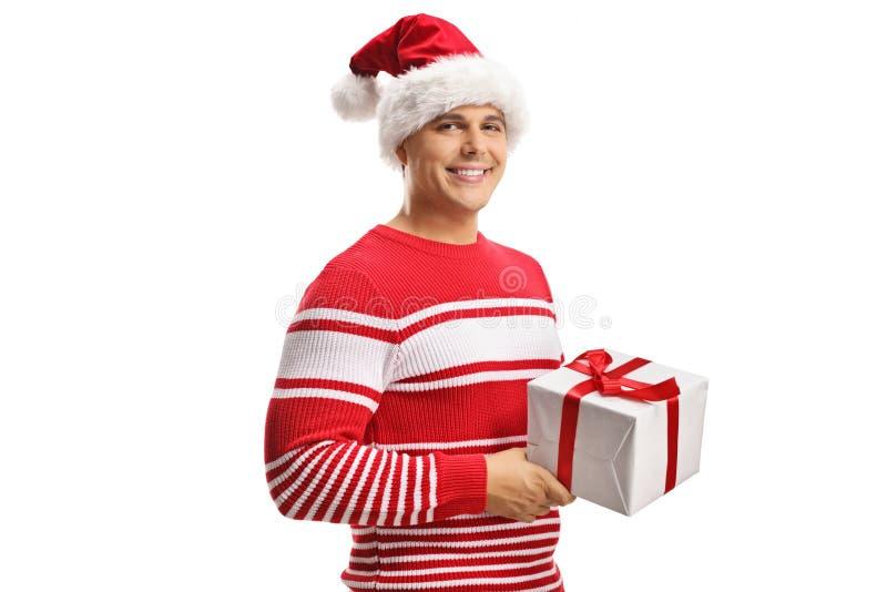 Ung man som bär en Santa Claus hatt och rymmer en julgåvaask arkivfoto