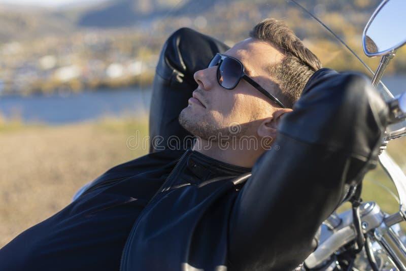Ung man som bär ett svart läderomslag, solglasögon och jeans l royaltyfri fotografi