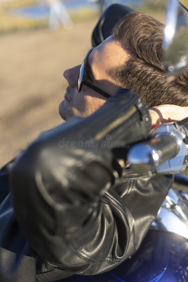 Ung man som bär ett svart läderomslag, solglasögon och jeans l arkivbild