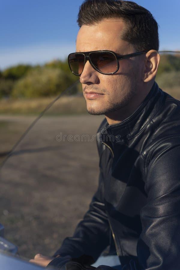 Ung man som bär ett svart läderomslag, solglasögon och jeans s arkivfoton