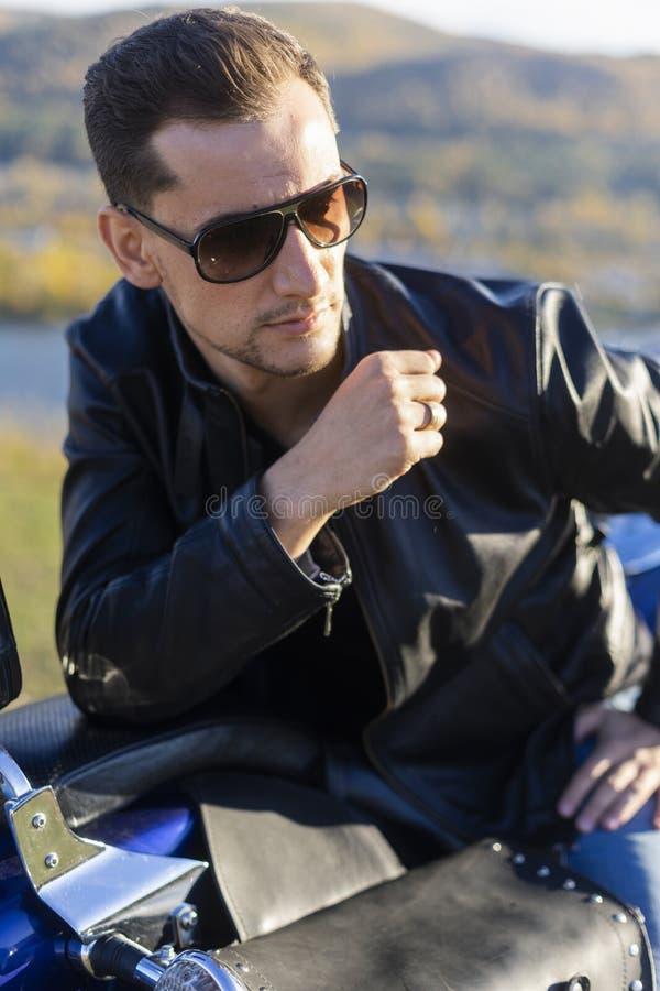 Ung man som bär ett svart läderomslag, solglasögon och jeans s royaltyfri fotografi