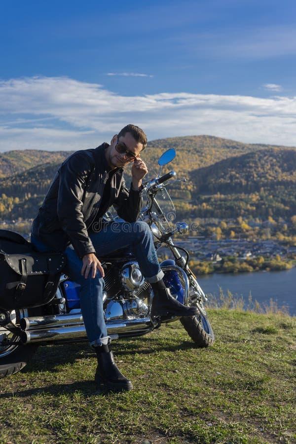 Ung man som bär ett svart läderomslag, solglasögon och jeans s arkivbilder