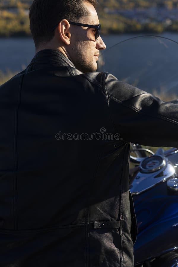 Ung man som bär ett svart läderomslag, solglasögon och jeans s arkivfoto
