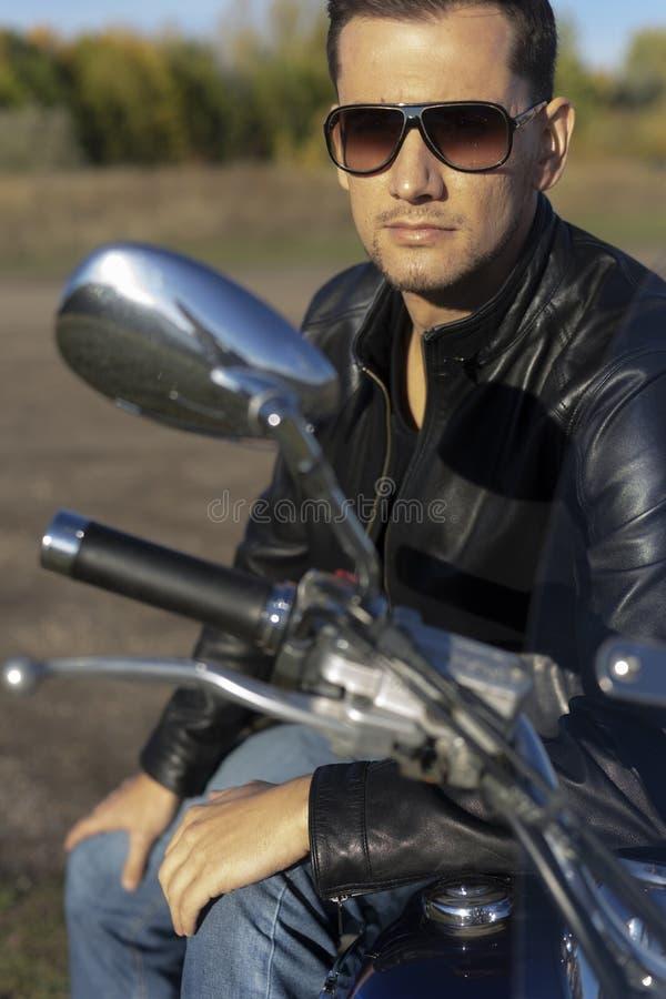Ung man som bär ett svart läderomslag, solglasögon och jeans s fotografering för bildbyråer