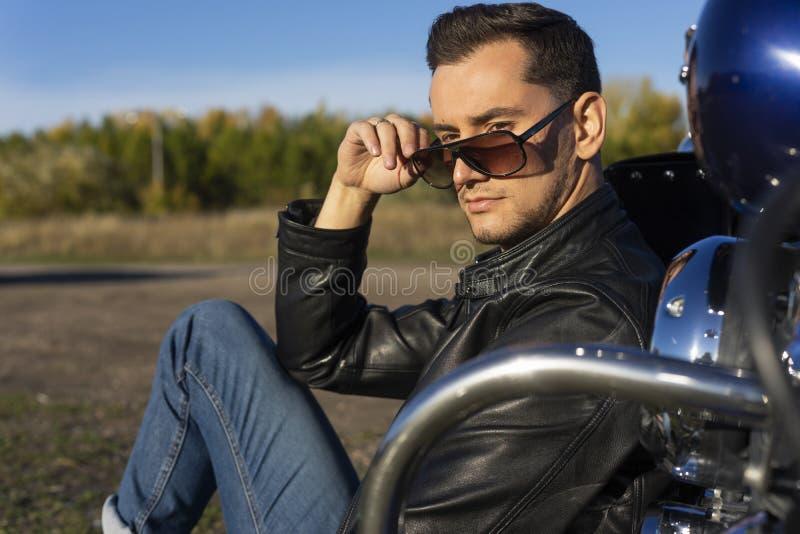 Ung man som bär ett svart läderomslag, solglasögon och jeans s royaltyfri foto