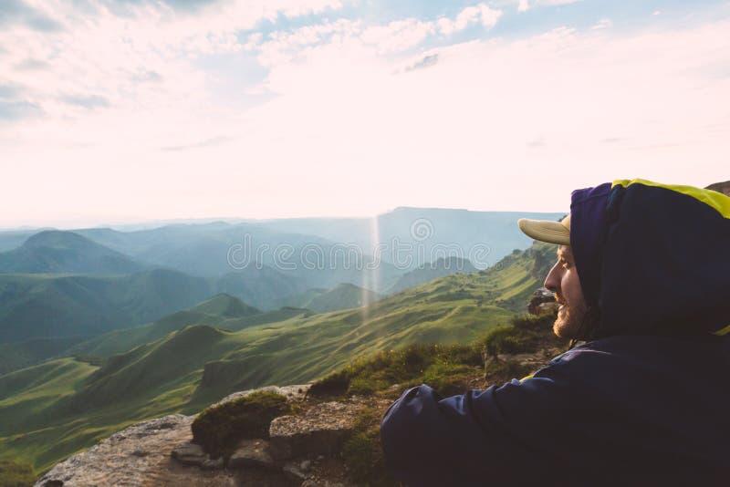 Ung man som bara sitter utomhus- solnedgångberg för grön dal på bakgrundslopplivsstil och överlevnadbegrepp arkivbild