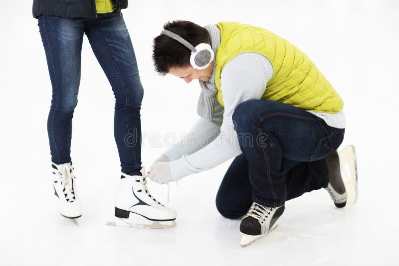 Ung man som binder skridskor på en åka skridskor isbana royaltyfri foto
